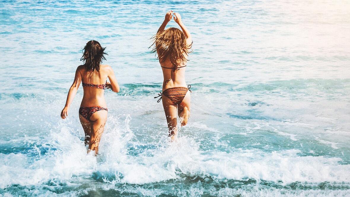 Deux femmes qui sautent à la mer se sentent bien dans leur peau, grâce au calcul de l'IMC pour les femmes.