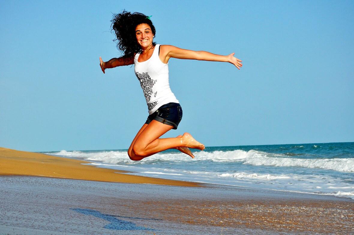 Une femme heureuse sur la plage grâce à un calcul régulier de l'IMC..