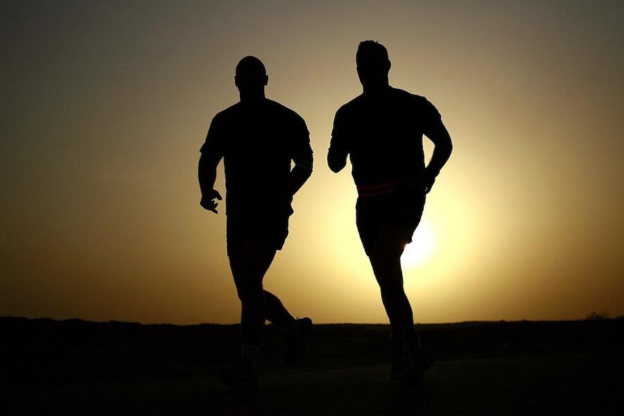 Dwóch mężczyzn, którzy łączą trening biegowy z kalkulatorem BMI dla mężczyzn.